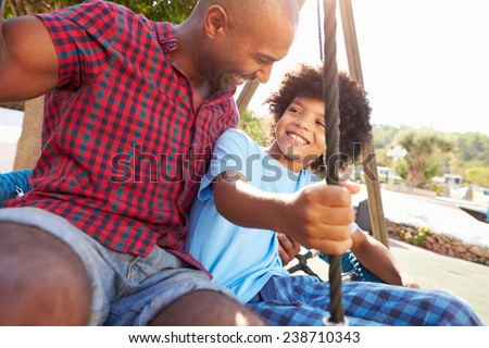 Father And Son Having Fun On Swing In Playground - stock photo
