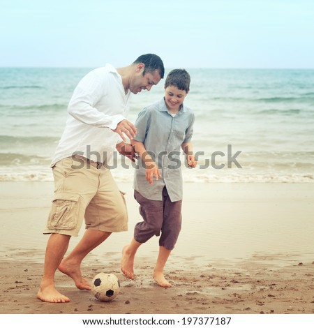 Father and son having fun on the beach and playing with a ball - stock photo