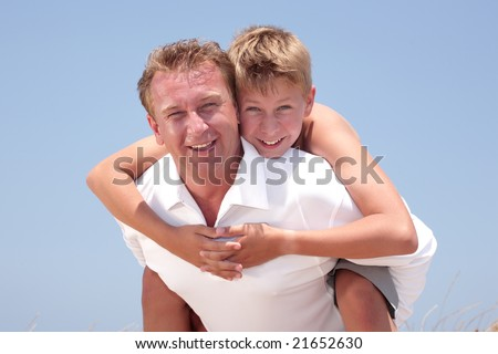 father and son having fun on the beach over sky background - stock photo