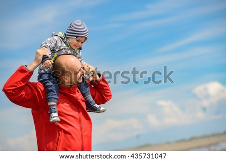 Father and son having fun on tropical beach. - stock photo