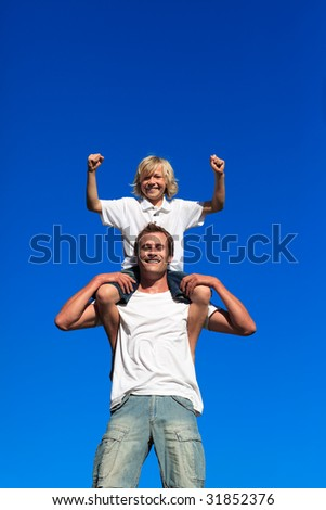 Father and son having fun outdoors against blue sky - stock photo