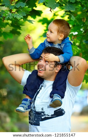 father and son having fun playing  in green park - stock photo