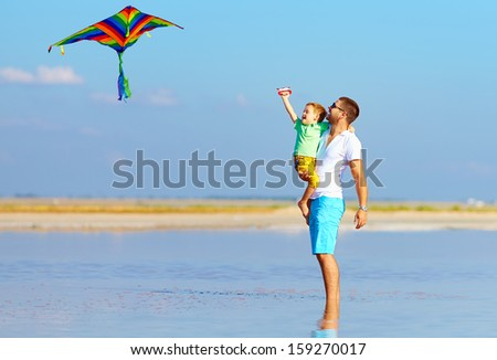 father and son having fun, playing with kite together - stock photo