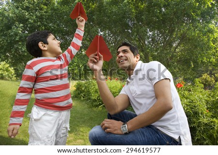 Father and son having fun with paper airplanes - stock photo