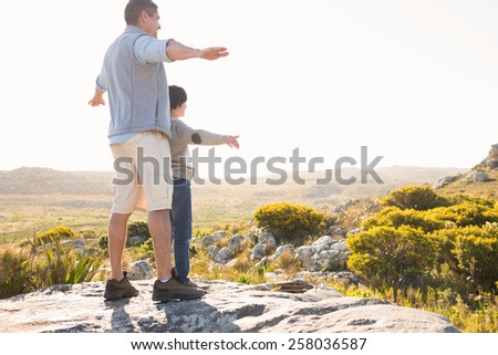 Father and son hiking through mountains on a sunny day - stock photo