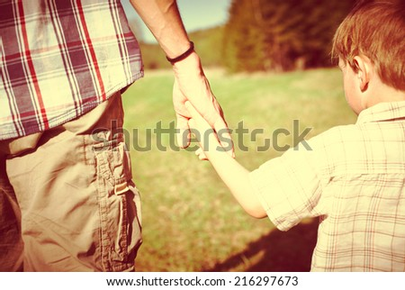 Father and son holding each other by hands - stock photo