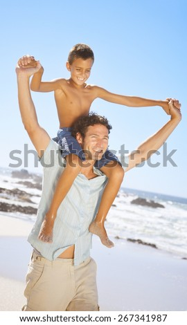 father and son holding hands while walking on sand at beach - stock photo