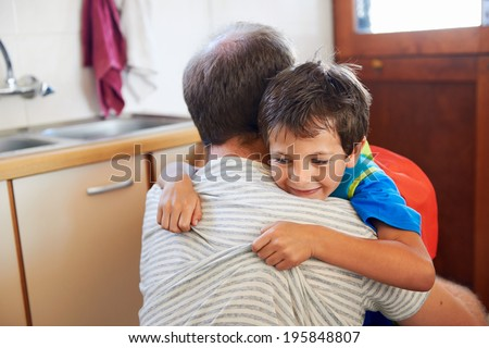 father and son hug goodbye before school love and affectionate embrace - stock photo