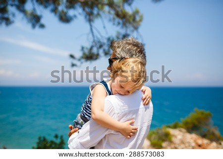 Father and son hugging on the blue sea background - stock photo