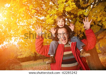 Father and son in autumn park - stock photo