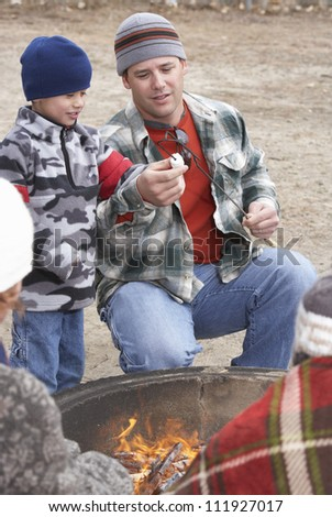Father and son in front of campfire ready to toast marshmallow - stock photo