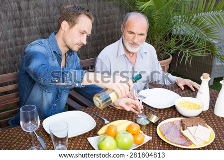 Father and son in garden having some wine - stock photo