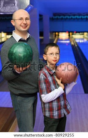 Father and son in glasses stands sideways and holds  balls for bowling - stock photo