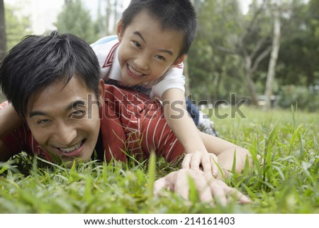Father and son (7-9) in park, lying in grass and laughing - stock photo