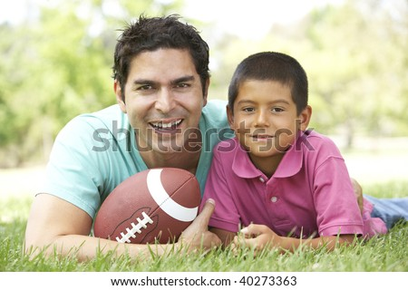 Father And Son In Park With American Football - stock photo