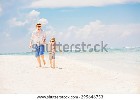 Father and son in summer nats and sunglasses running barefoot on the sea surf line having great holidays time on beautiful sunny day. Bali, Pandawa beach  - stock photo