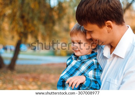 Father and son in the autumn park - stock photo