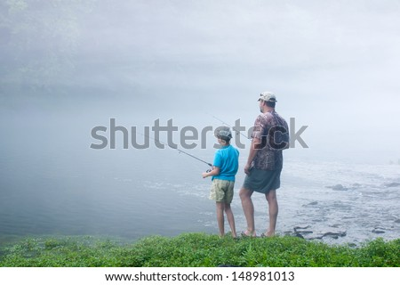 Father and son in the early misty morning fishing - stock photo