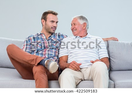 Father and son interacting with each other in living room - stock photo