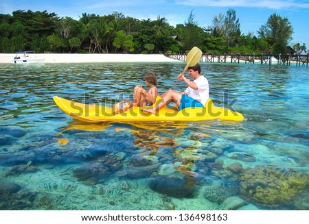 Father and son kayaking next to a tropical coral island - stock photo
