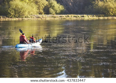 Father and son kayaking on a lake, back view, distant - stock photo
