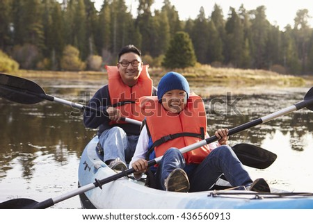 Father and son kayaking on a rural lake, front view - stock photo