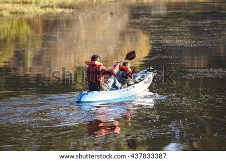 Father and son kayaking together on a lake, back view - stock photo