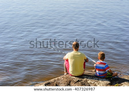 Father and son lake fishing together. They're using telescopic fishing rods, fishing line, floats, and baited fishing hooks. Man has tattoos. - stock photo