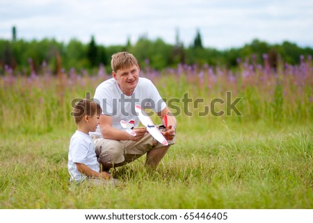 Father and son launch plane model in summer field - stock photo