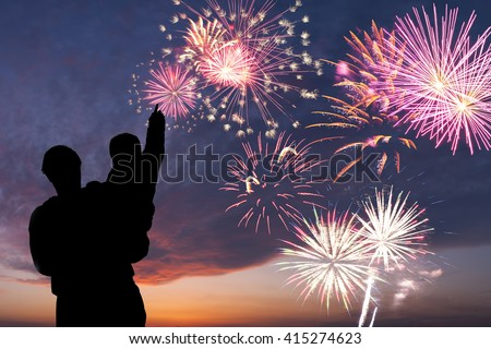 Father and son look at holiday firework in sky, happy family - stock photo