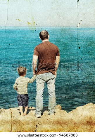 Father and son looking at a white sail in the sea. Photo in old image style. - stock photo
