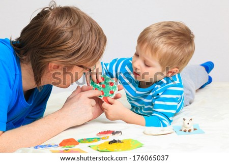 father and son looking at baby crafts, early education - stock photo