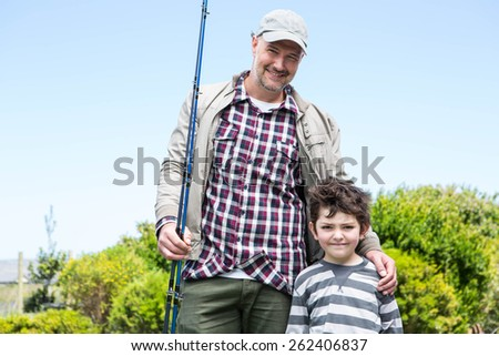 Father and son looking at camera in the countryside - stock photo
