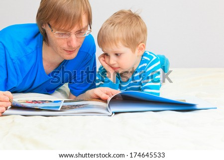 father and son looking at family photo album at home - stock photo