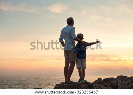 Father and son looking on sunset at the sea - stock photo