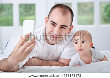 Father and son looking to phone and taking selfie - stock photo