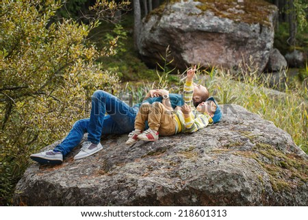 Father and son lying on a rock and looking at the sky. - stock photo
