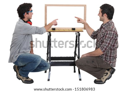 Father and son making wooden frame - stock photo