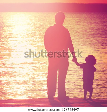 Father and son  on a dock at sunset, boy looking up at his father. - stock photo