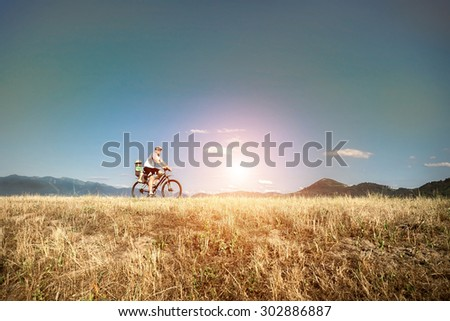 Father and son on bicycle under sunlight. - stock photo
