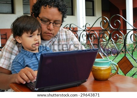 Father and son on computer together - stock photo