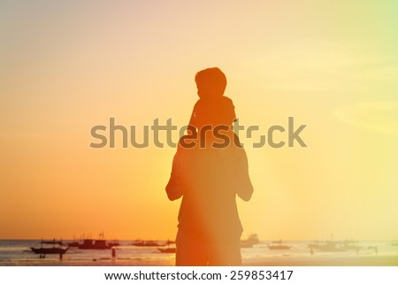 father and son on shoulders looking at sunset on the beach - stock photo