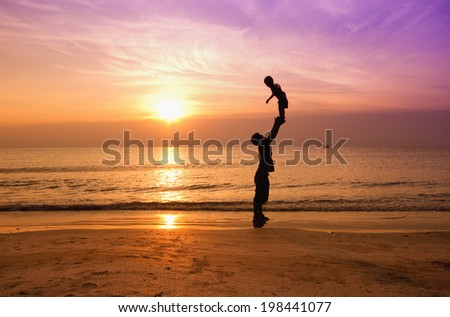 father and son on sunset beach,silhouette - stock photo