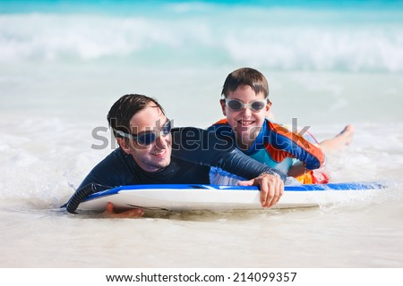 Father and son on vacation having fun surfing on boogie board - stock photo