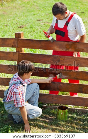 Father and son painting a garden fence on a sunny summer day - stock photo
