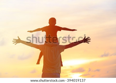 father and son play on sunset sky - stock photo