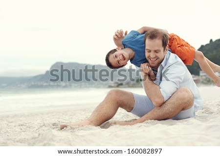 Father and son playing at beach together portrait fun happy lifestyle - stock photo