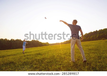 Father and son playing at sunset. Paper airplanes. - stock photo