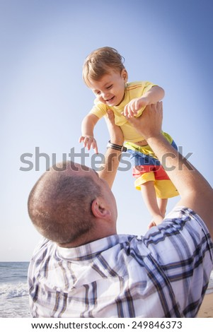 Father and son playing at the beach - stock photo