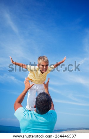 Father and son playing at the beach in the day time - stock photo